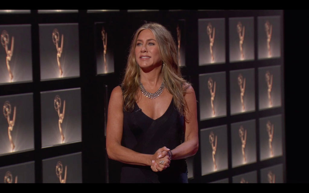 Jennifer Aniston stands backstage at the Emmy Awards. She's wearing a black dress with a large silver necklace and her golden hair is down.