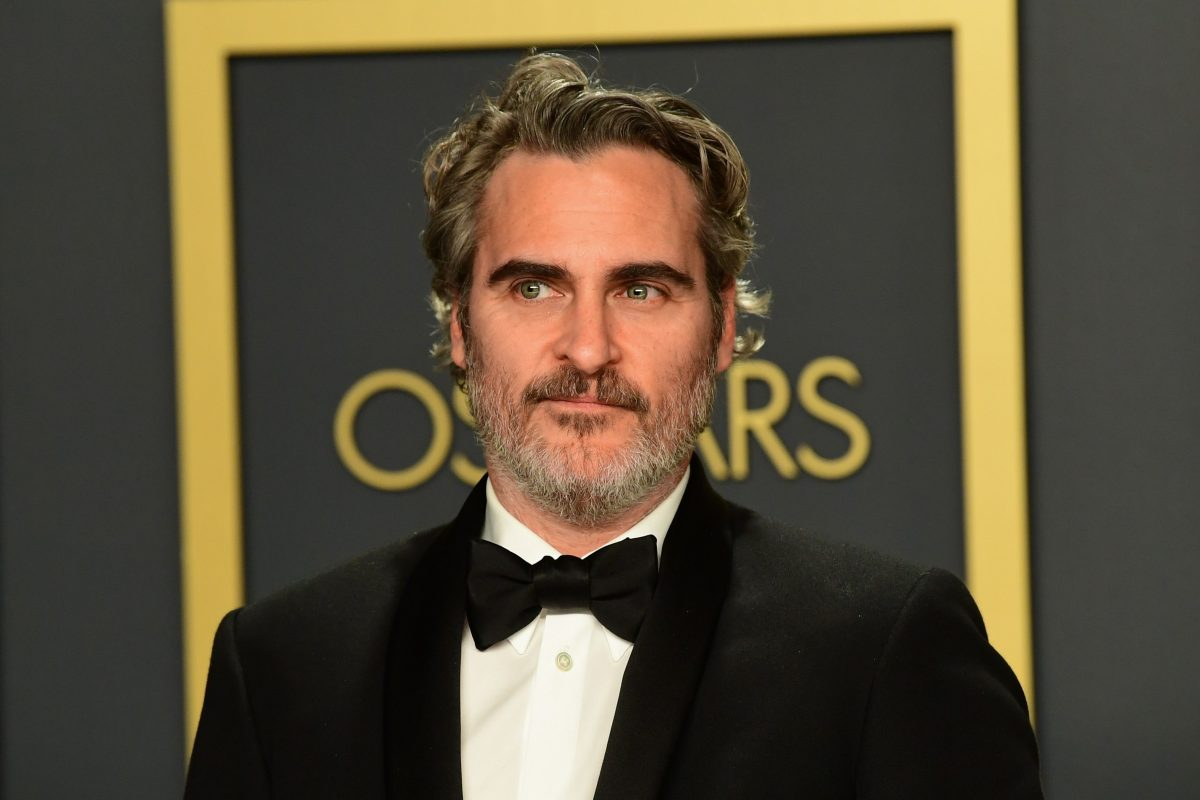 Joaquin Phoenix in a black tux, posing in the press room at the Oscars in 2020.