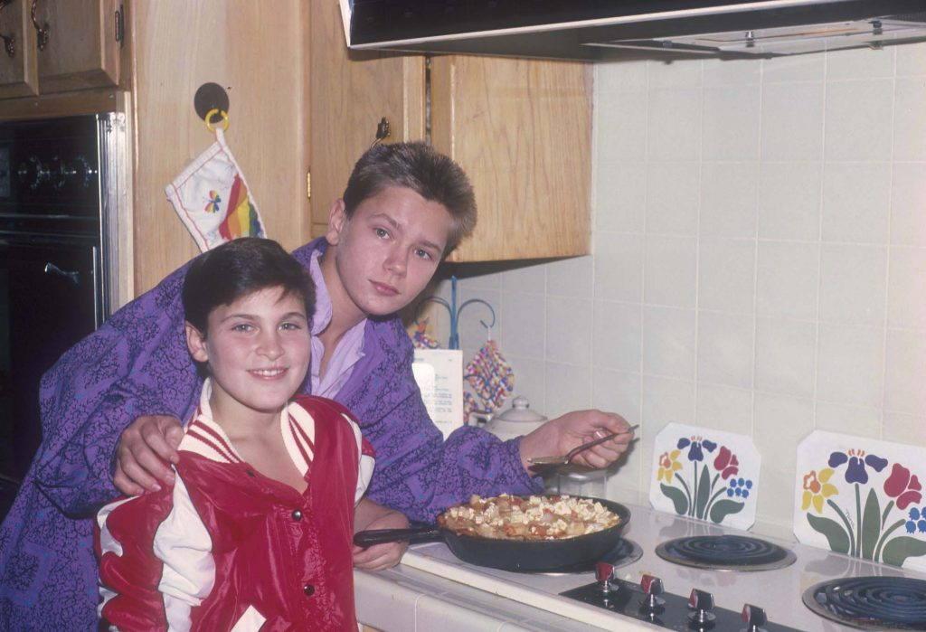 Joaquin and River Phoenix smiling, cooking in their home, 1985