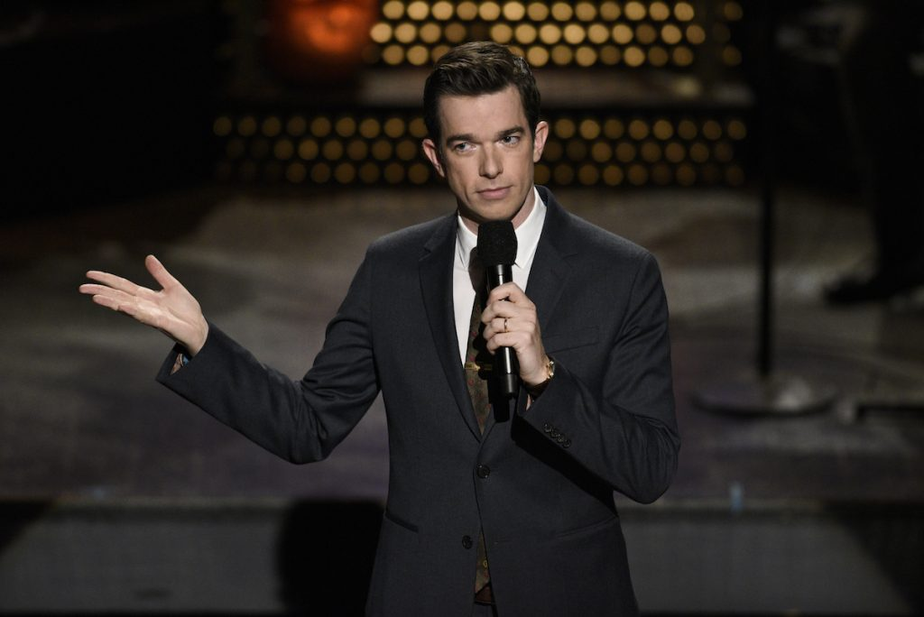 John Mulaney holds a microphone and makes hand gestures on stage.