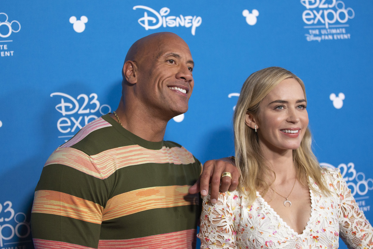 Dwayne Johnson and Emily Blunt with blue D23 background