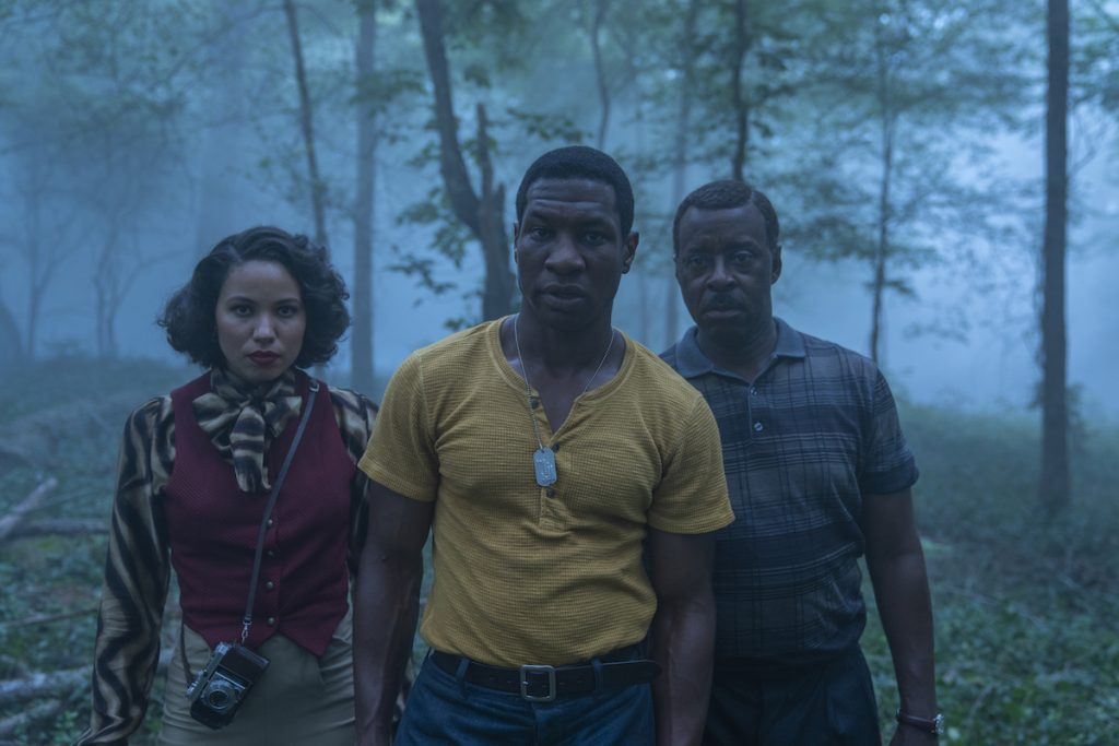 Jurnee Smollett, Jonathan Majors, and Courtney B. Vance standing in an open field in 'Lovecraft Country.'