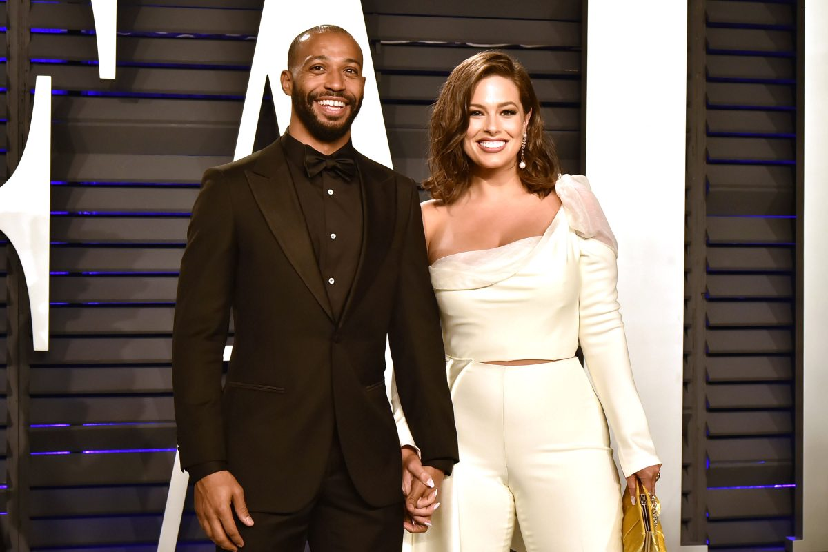 Justin Ervin in a black suit and Ashley Graham in a cream colored shirt and pants.