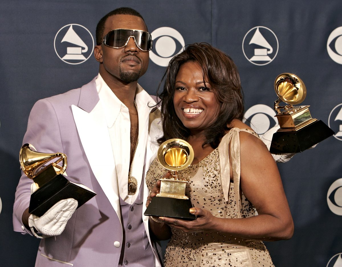 Kanye West and his mom, Donda, holding his three Grammy Awards while smiling for the camera on the red carpet.
