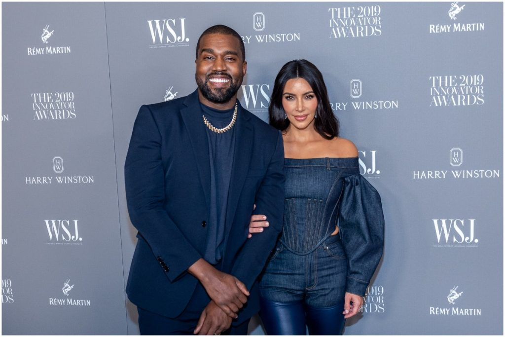 Kanye West and Kim Kardashian embracing each other and smiling on the red carpet.