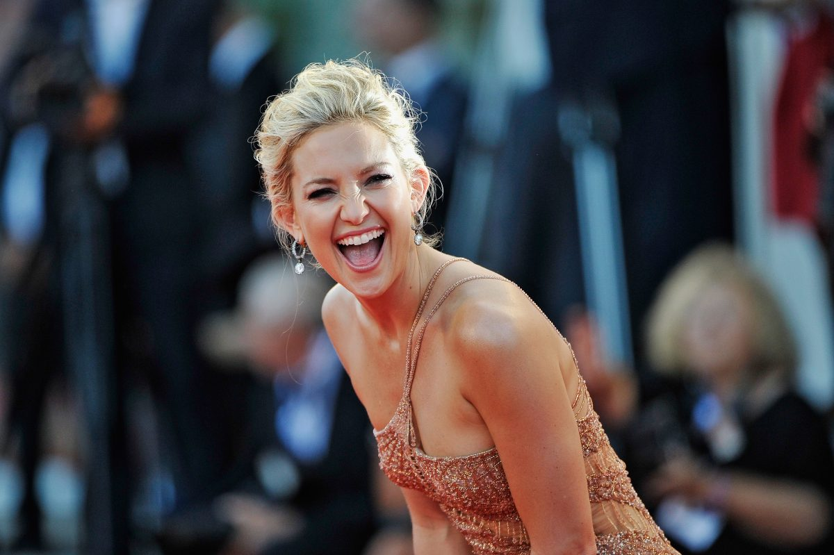 Kate Hudson beaming and laughing at the camera at a red carpet event.