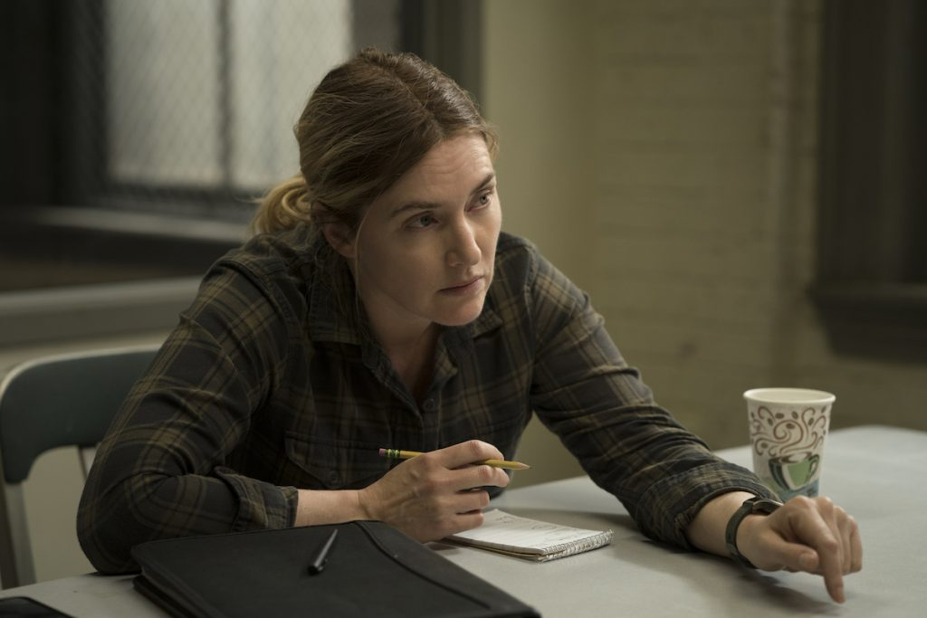 Kate Winselt sitting in a police station in 'Mare of Easttown.'