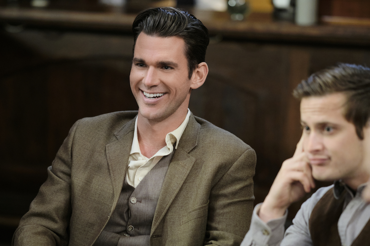 Smiling Kevin McGarry as Nathan Grant sitting next to Aren Buchholz as Jesse in episode of 'When Calls the Heart' Season 8