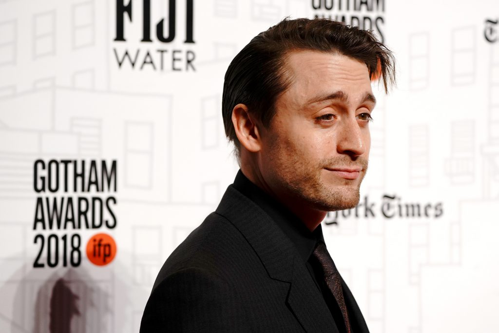Kieran Culkin, from chest up, standing in front of a white backround with his side face toward the camera.