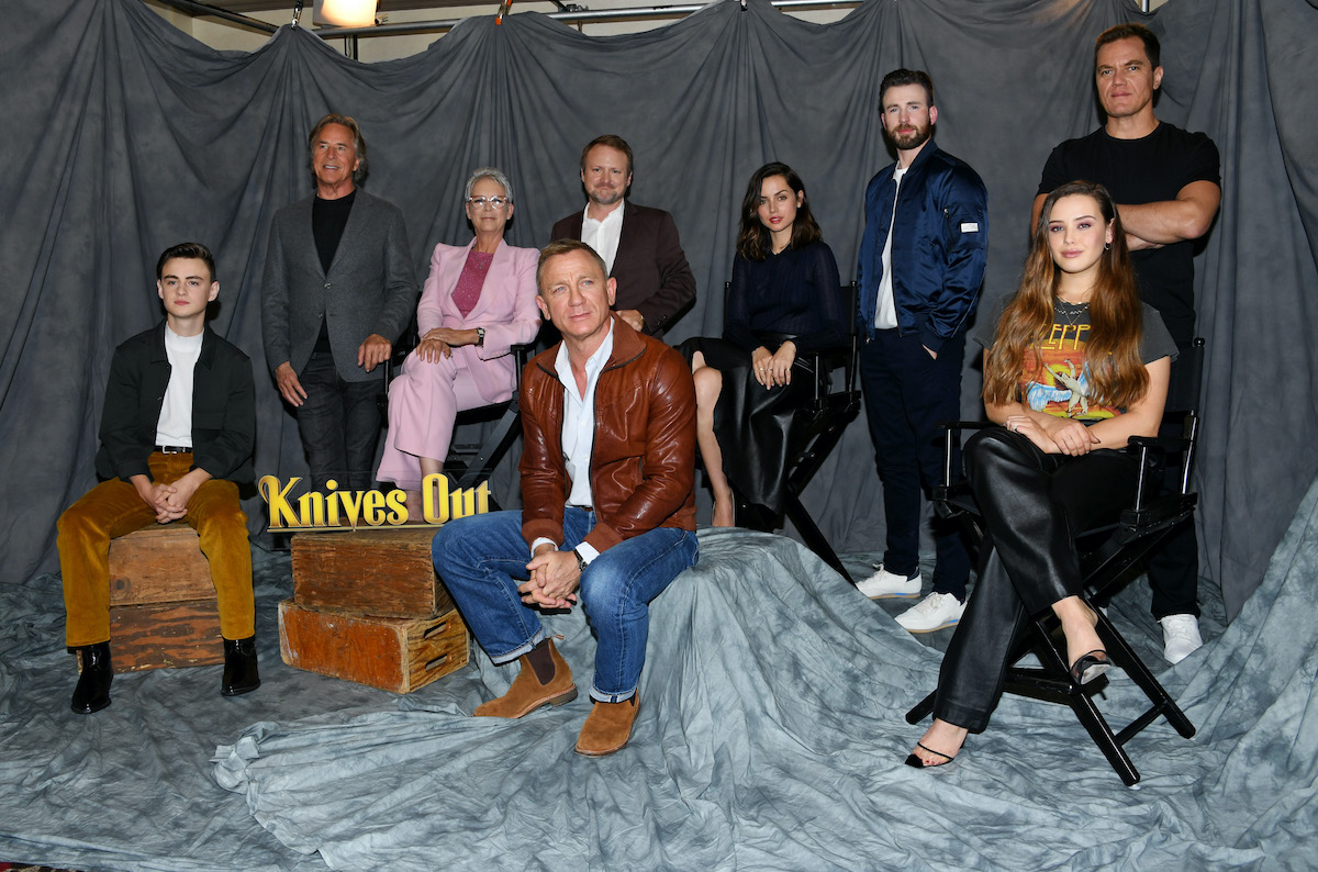 Jaeden Martell, Don Johnson, Jamie Lee Curtis, Rian Johnson, Daniel Craig, Chris Evans, Ana de Armas, Michael Shannon, and Katherine Langford of 'Knives Out' pose in front of a grey backdrop. 'Knives Out 2' filming wrapped in September 2021 and will star Craig with a new cast.
