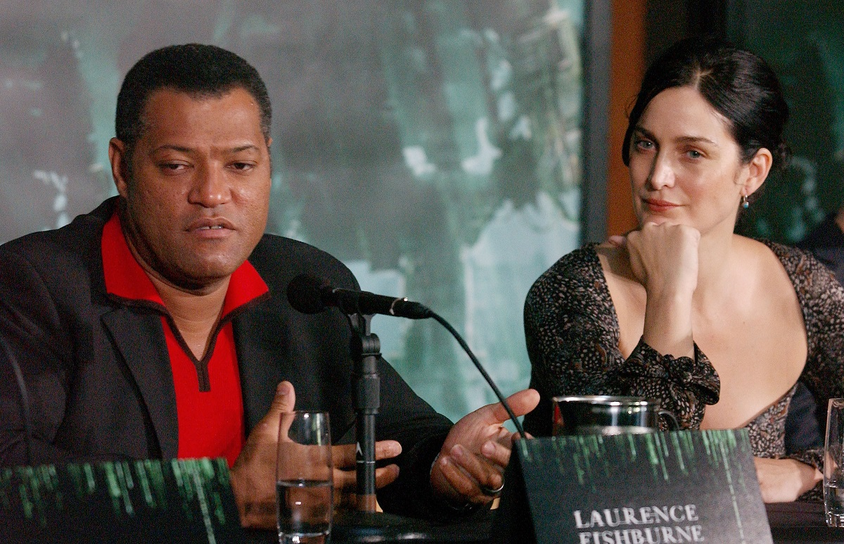 Carrie-Anne Moss with her hand on her chin looks at Laurence Fishburne as he speaks into a microphone at an event for 'The Matrix.'