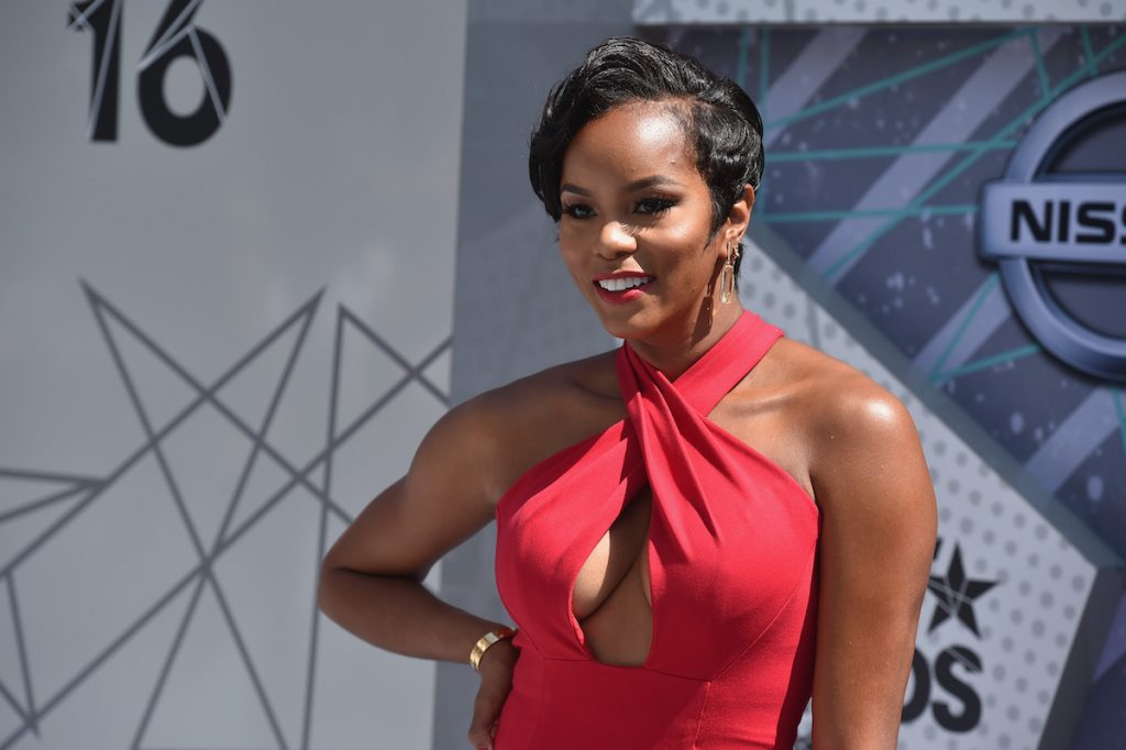 Letoya Luckett smiling in a red dress on the BET Red Carpet