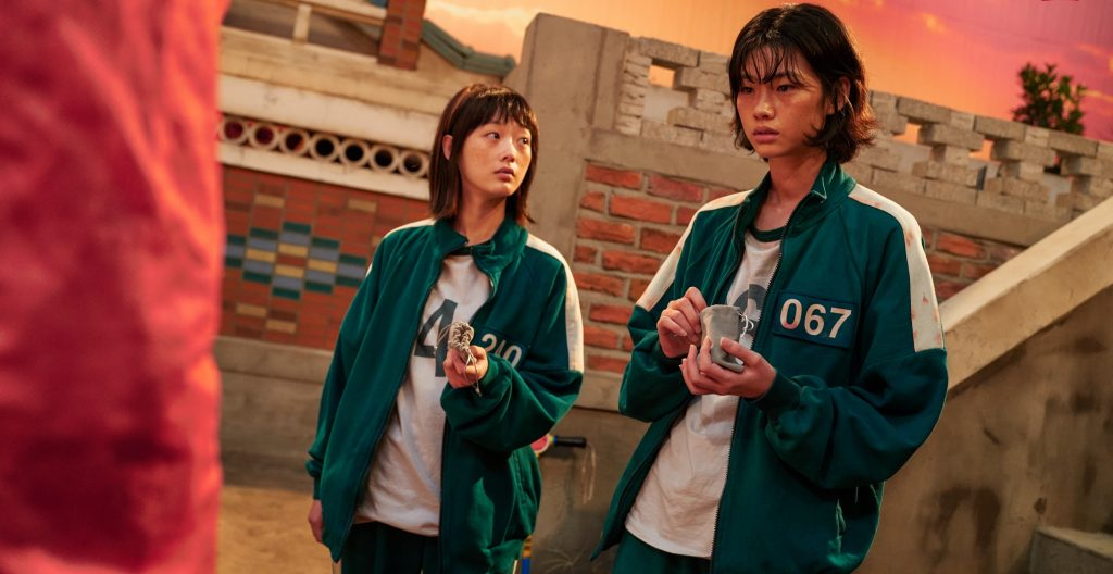 Lee Yoo-Mi as Ji-Yeong and Jung Ho-Yeon as Kang Sae-Byeok for Netflix's 'Squid Game' wearing green tracksuits and holding marbles