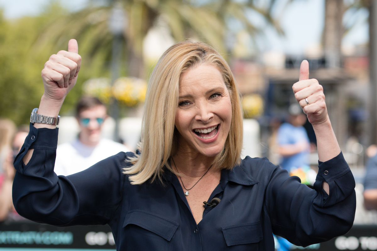 Lisa Kudrow gives two thumbs up and smiles. She is wearing a navy blue button-down shirt.