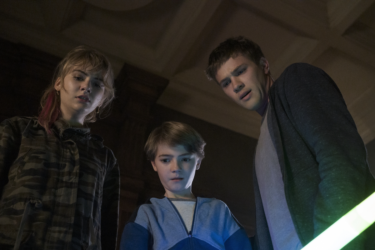 Kinsey (Emilia Jones), Tyler (Connor Jessup), and Bode (Jackson Robert Scott) look down upon something in a production still from 'Locke and Key' Season 1.
