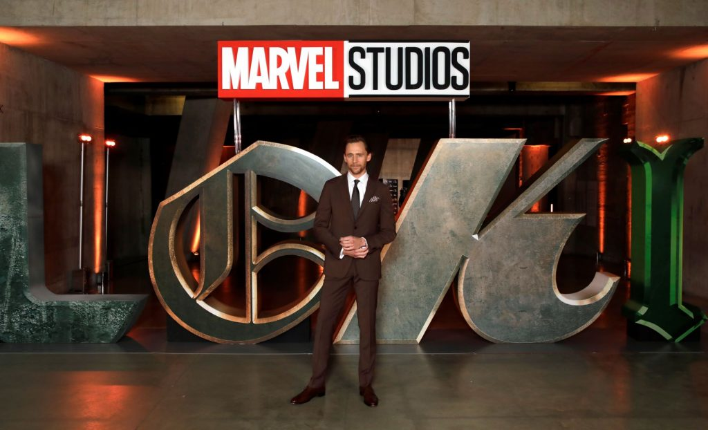 'What If...?' star Tom Hiddleston wears a suit and tie and poses in front of a huge 'Loki' sign.