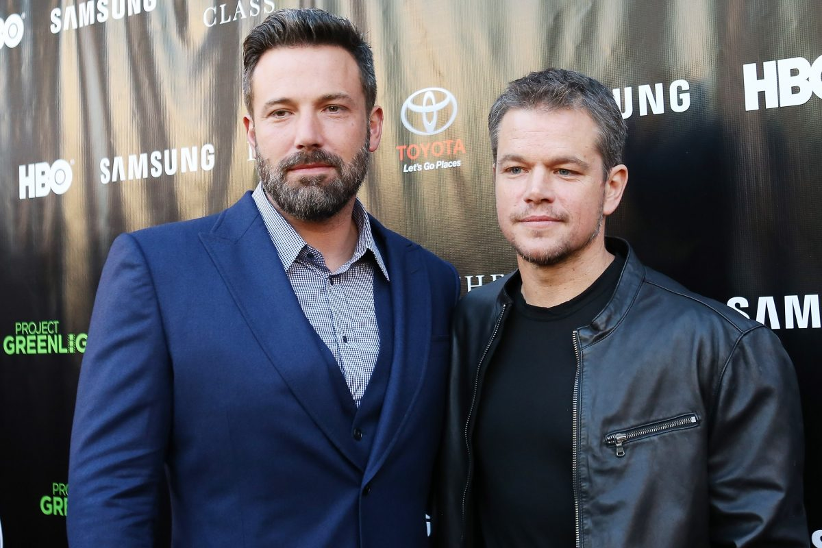 Ben Affleck, in a blue suit with a blue shirt, and Matt Damon, in a black t-shirt and black leather jacket, at an event in 2015.