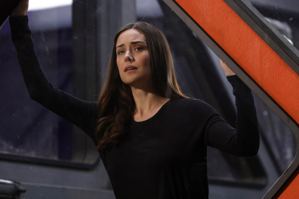 Megan Boone as Liz Keen stands on the edge of the container box the task force team put her in. She's dressed in all black.