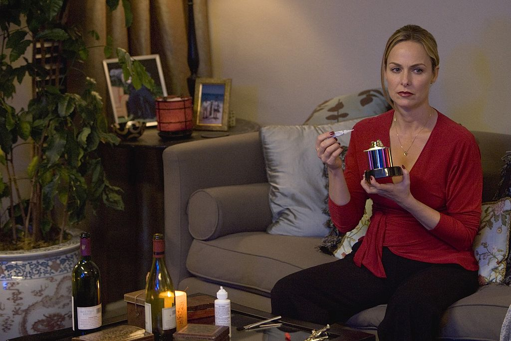 Melora Hardin as Jan Levinson sits on the couch in a red shirt.