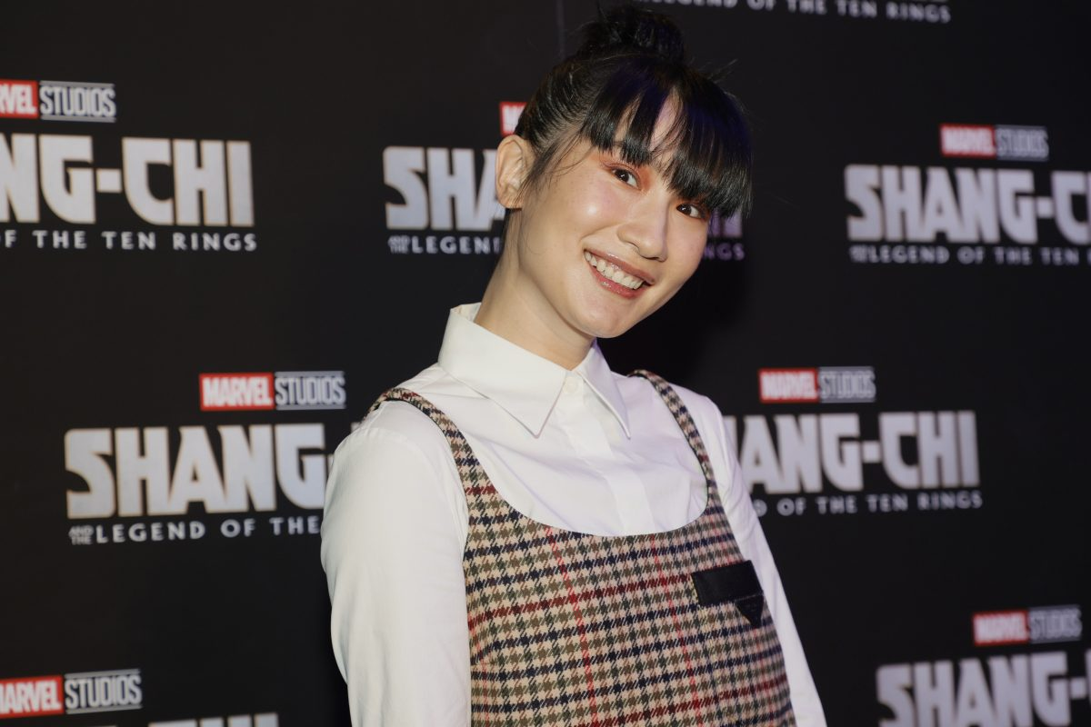 Meng'er Zhang, in a white shirt and checkered dress, smiling at the camera at a screening for her movie 'Shang-Chi and the Legend of the Ten Rings.'