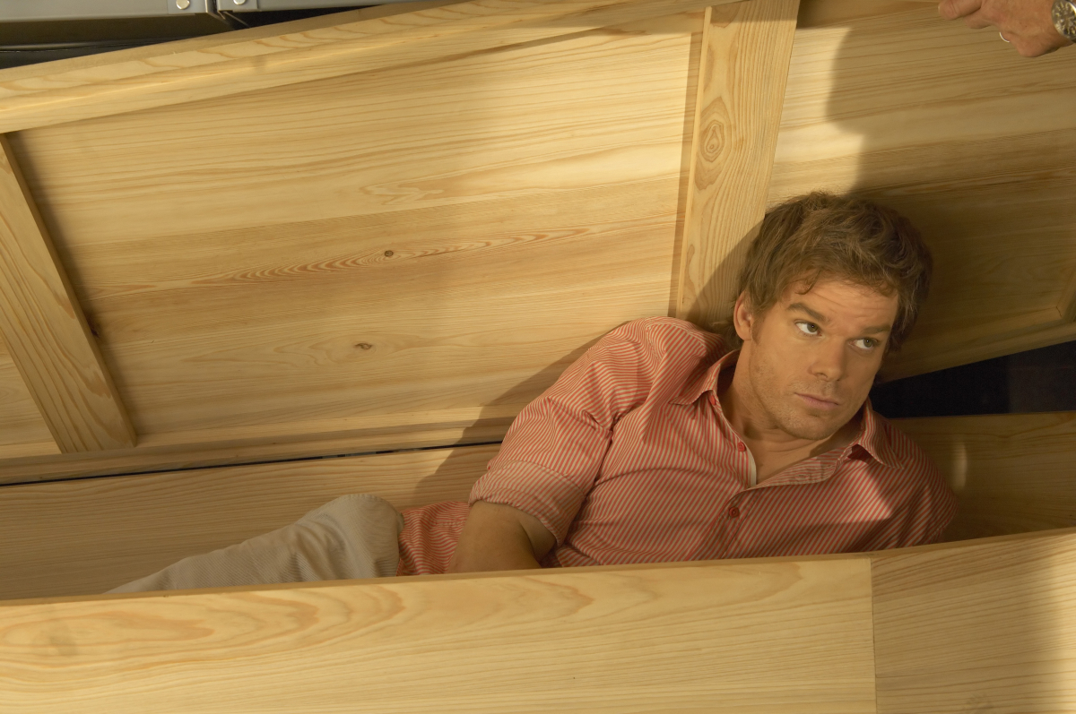Dexter morgan sits in an open wooden coffin in 'Dexter.' He is wearing a salmon button-down shirt.