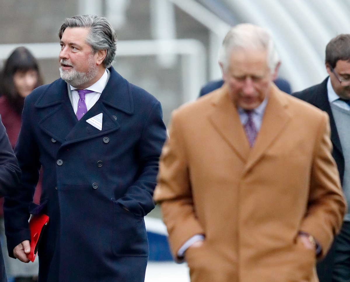 Michael Fawcett walks behind Prince Charles wearing a blue coat at The Prince's Countryside Fund Raceday