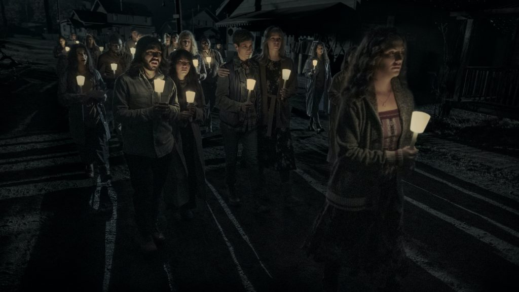 Cast members in a scene from 'Midnight Mass' holding candles while walking as a group