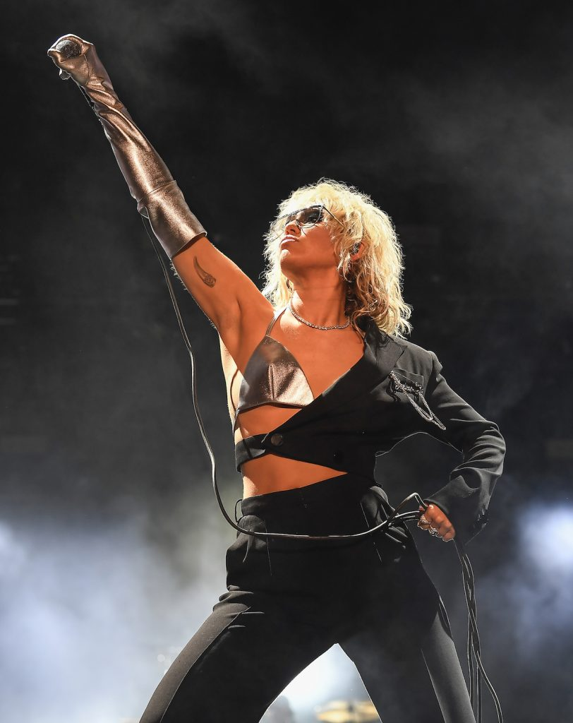 Miley Cyrus raises a microphone to the sky while performing on stage in a black and silver outfit.
