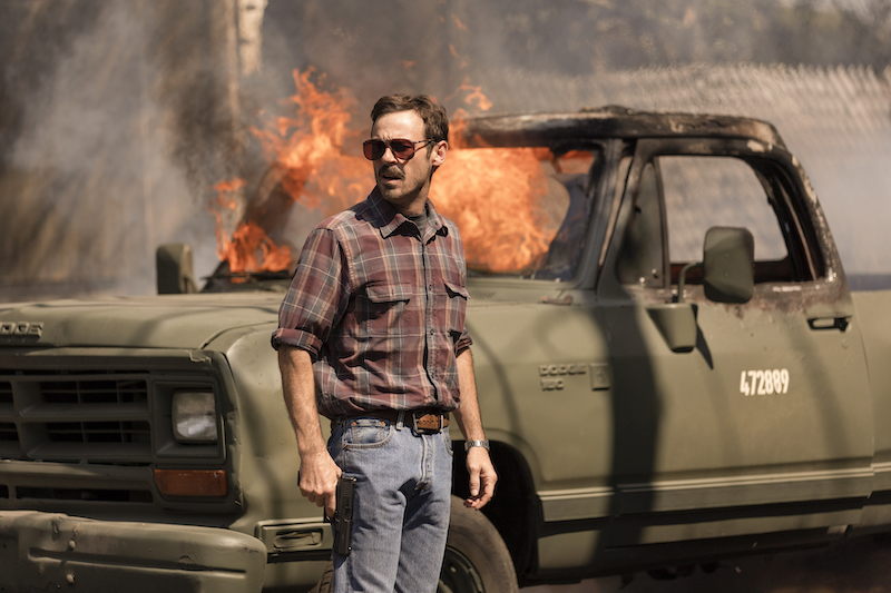 Scoot McNairy as Walt Breslin stands in front of a truck in flames.