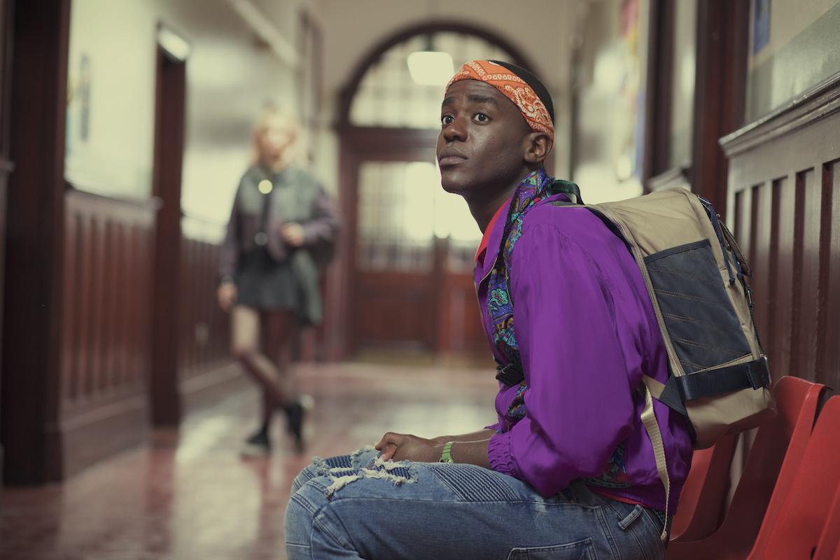Ncuti Gatwa sitting down in a chair in 'Sex Education' Season 1