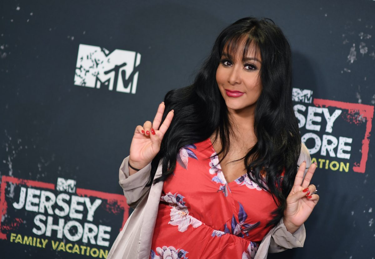 Nicole 'Snooki' Polizzi smiling and giving peace signs in front of an MTV 'Jersey Shore: Family Vacation' backdrop