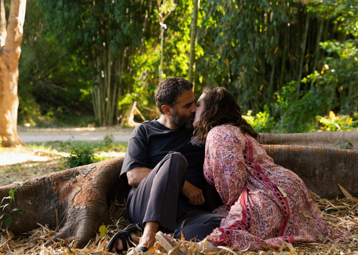 Bobby Cannavale as Tony and Melissa McCarthy as Frances in Hulu's 'Nine Perfect Strangers' Episode 6. They're kissing beneath a tree. Frances wears a pink dress and Tony wears dark pants and a black T-shirt.