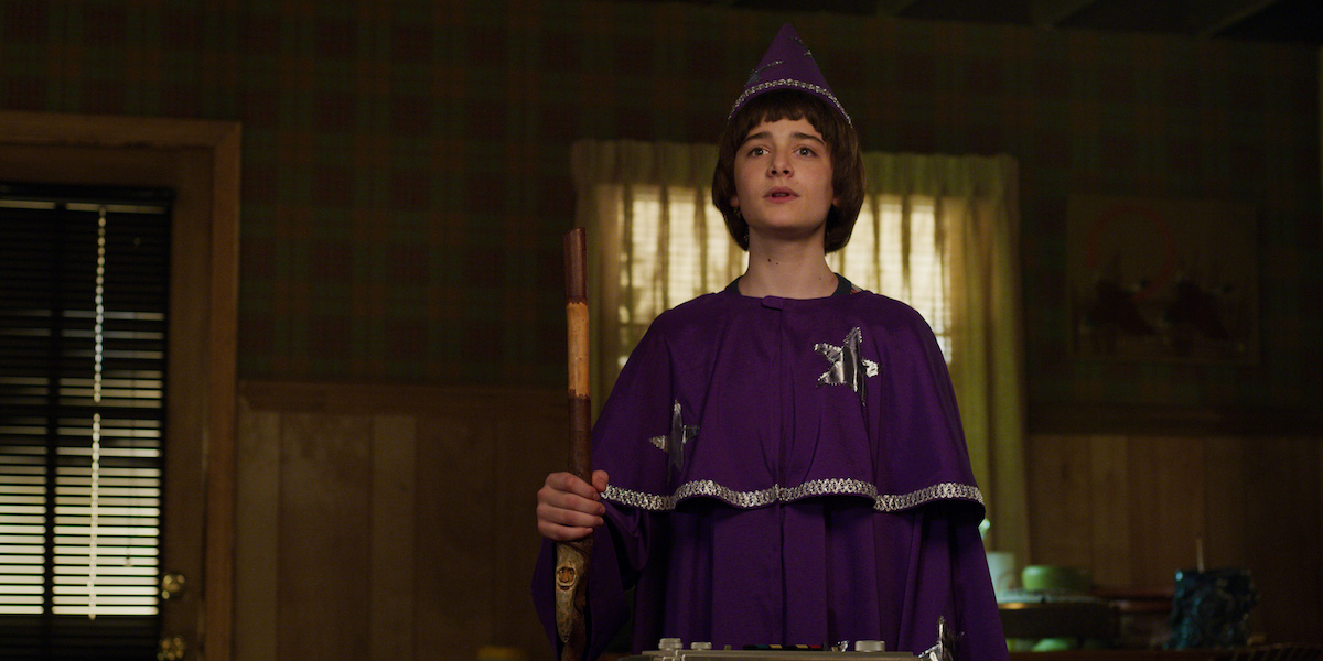 Will Byers (Noah Schnapp) dressed as Will the Wise in a purple wizard's robe and hat in a production still from 'Stranger Things' Season 3.