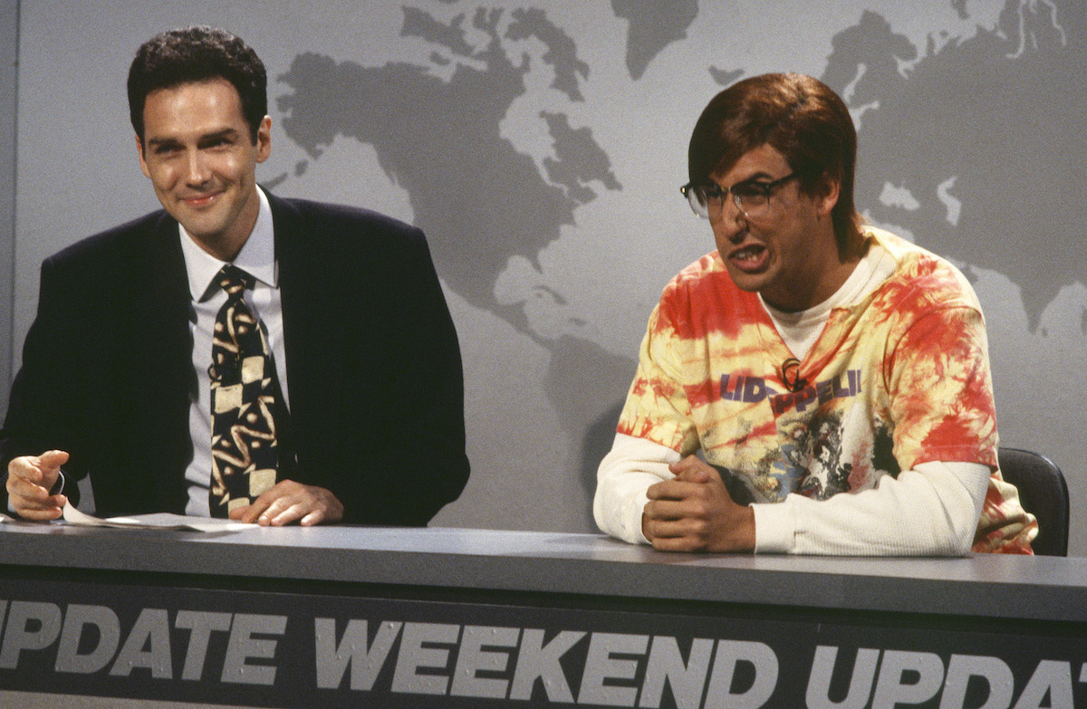Norm Macdonald and Adam Sandler on 'Saturday Night Live' in 1994. They sit at the Weekend Update desk, Macdonald in a suit and Sandler in a bright orange shirt and black glasses and wig. In 1995, Macdonald and Sandler co-starred in 'Billy Madison,' their first film together.