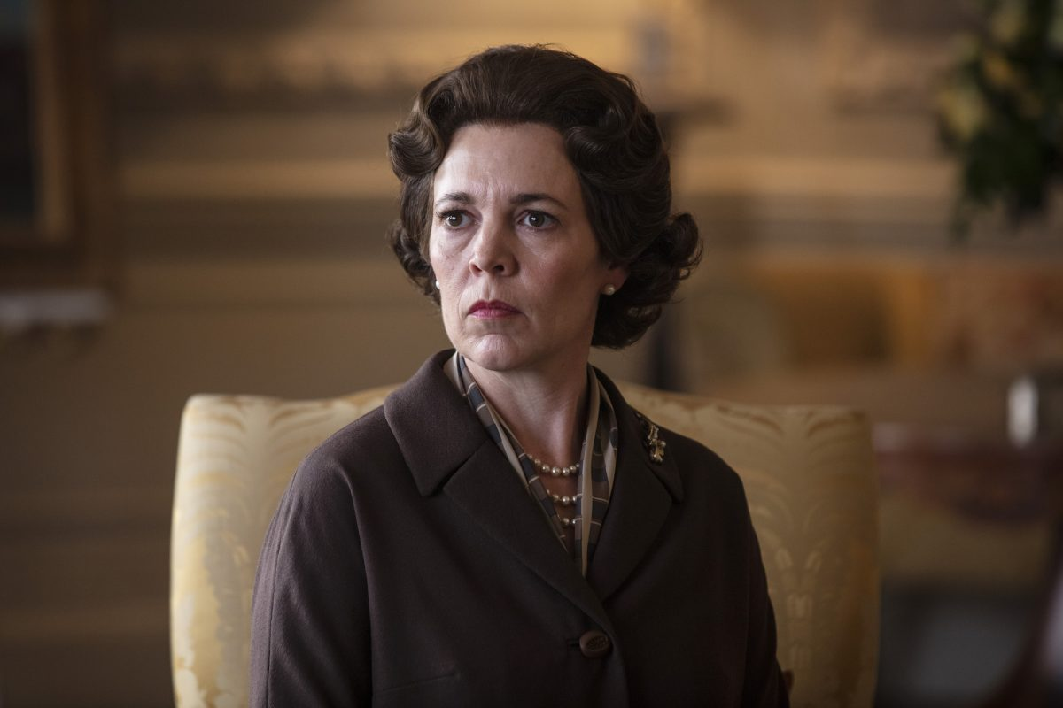 Olivia Colman sitting in a gold colored chair in 'The Crown.'