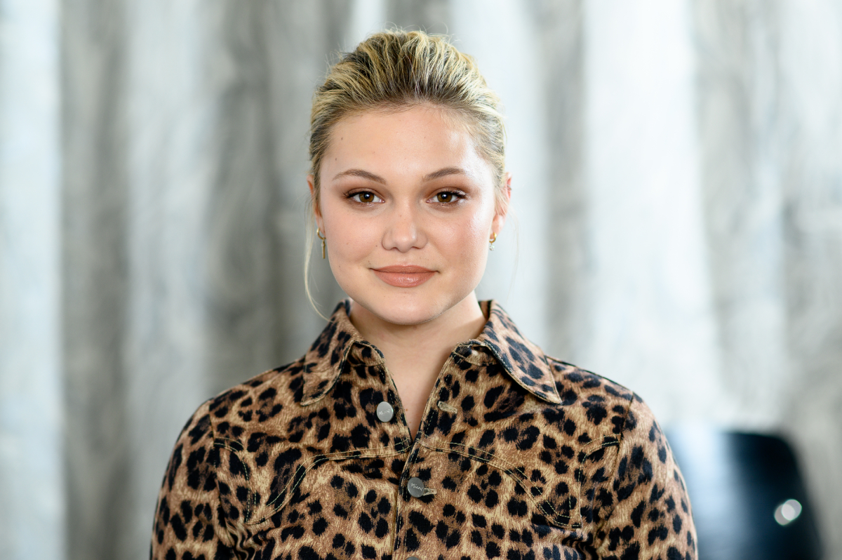Olivia Holt with her hair up, wearing an animal print jacket.