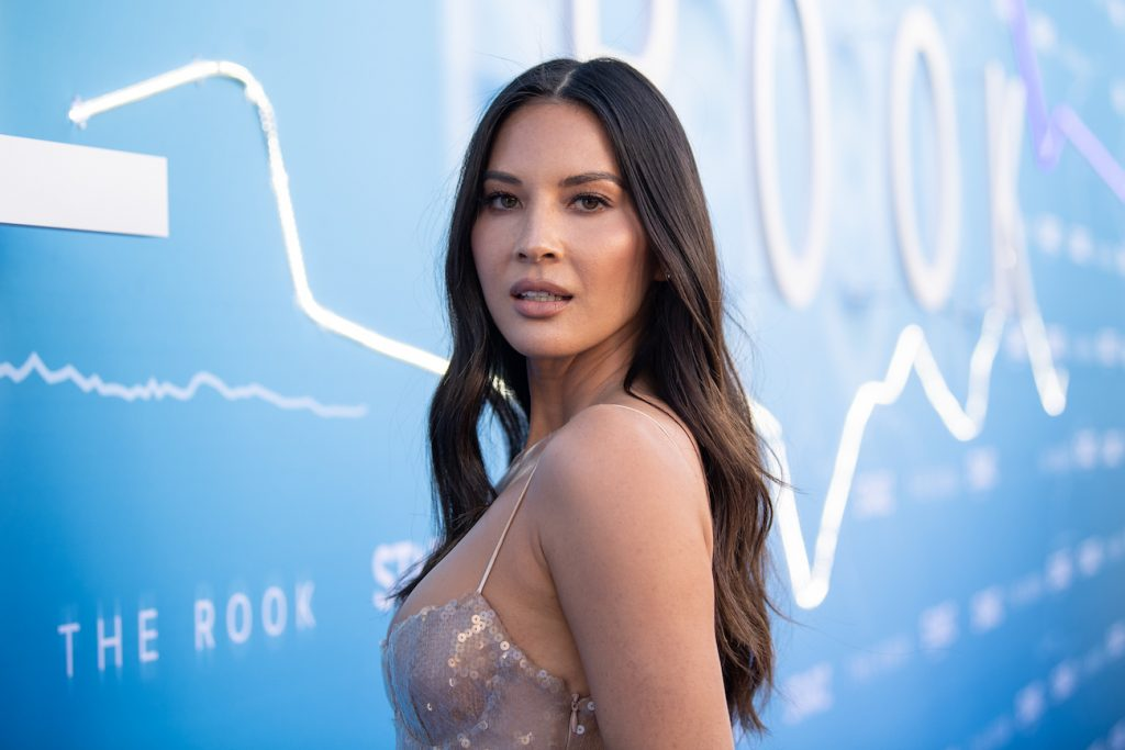 Olivia Munn looking into the camera in front of a blue background