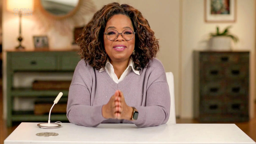 Oprah Winfrey speaks to the camera with her hands folded. She's wearing a lavender sweater and glasses.