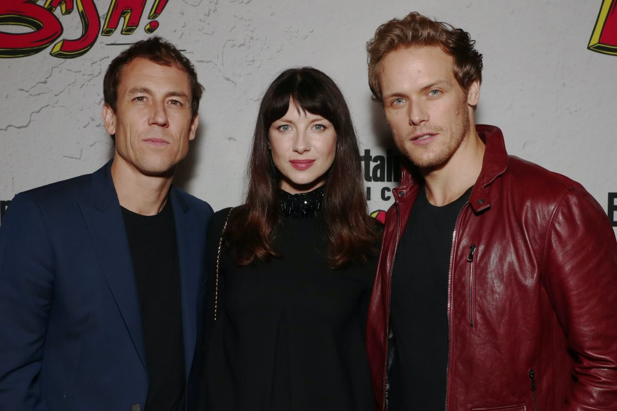 'Outlander' stars Tobias Menzies, Caitriona Balfe, and Sam Heughan pose at Comic-Con 2017 in San Diego in front of a white backdrop with red and yellow lettering. Menzies wears a black shirt and navy blue suit jacket. Balfe wears a black dress. Heughan wears a black shirt and red leather jacket. Heughan and Menzies shared many scenes in 'Outlander' as Jamie Fraser and Jack Randall. Menzies won an Emmy at the 2021 Emmy Awards on Sept. 19, and Heughan's reaction to Menzie's Emmy win was so supportive.