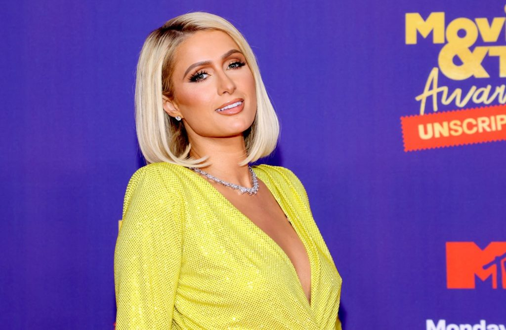 Paris Hilton in a yellow long-sleeved top in front of a blue background.