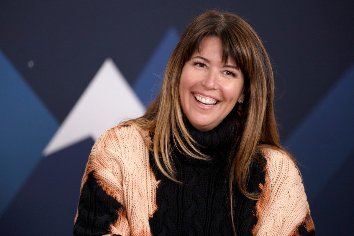 'Wonder Woman: 1984' director Patty Jenkins. Her brown hair is straight and down. She's wearing a black sleeveless shirt and smiling.