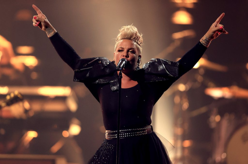 Pink performing on stage in an all-black outfit.