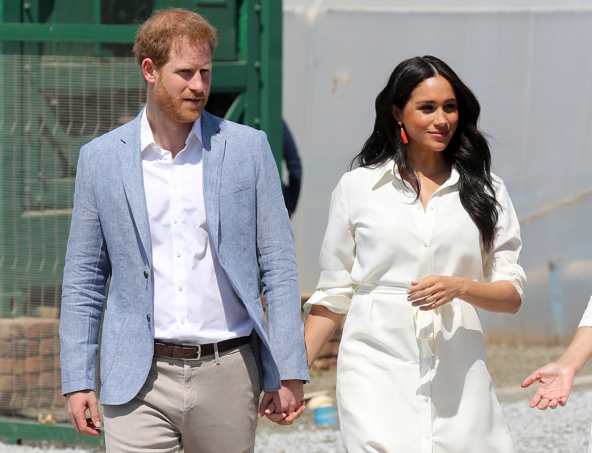 Prince Harry and Meghan Markle holding hands during tour in Johannesburg, South Africa