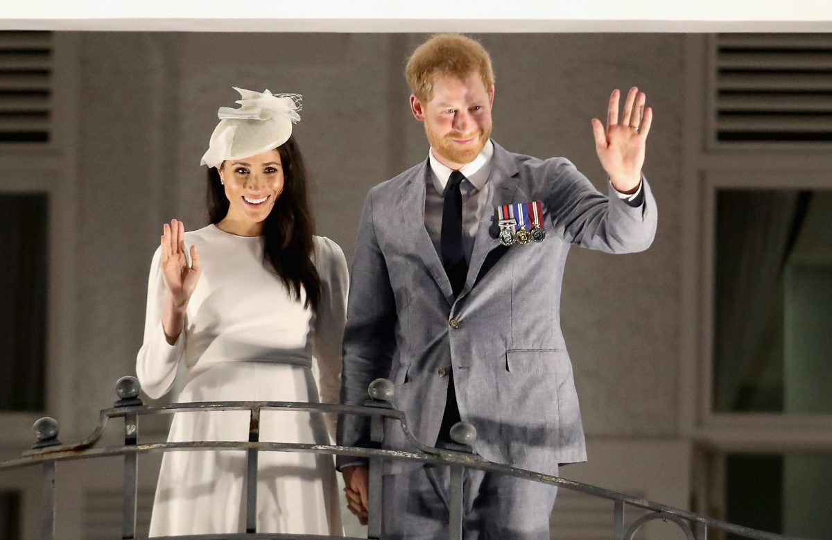 Prince Harry and Meghan Markle waving from the balcony of the Grand Pacific Hotel in Suva