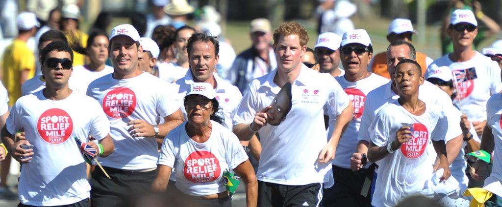 Prince Harry runs while holding a mask of Prince William