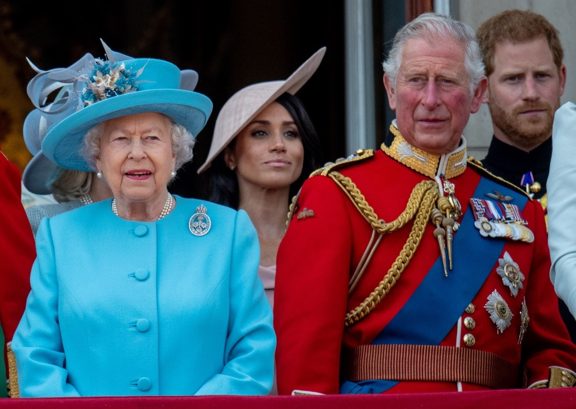Queen Elizabeth II, Prince Charles, Prince Harry, and Meghan Markle standing on Buckingham Palace balcony during Trooping the Colour.