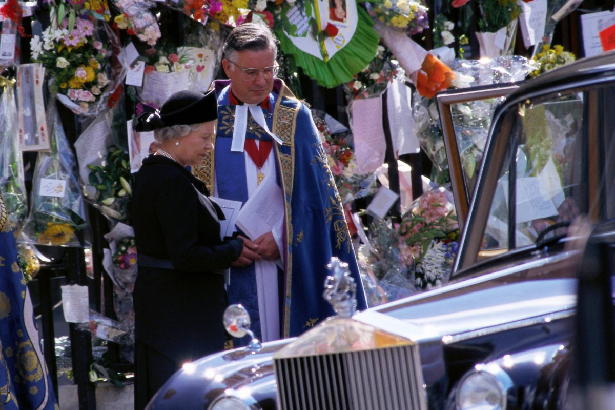 Queen Elizabeth stands with a priest at the funeral of Princess Diana