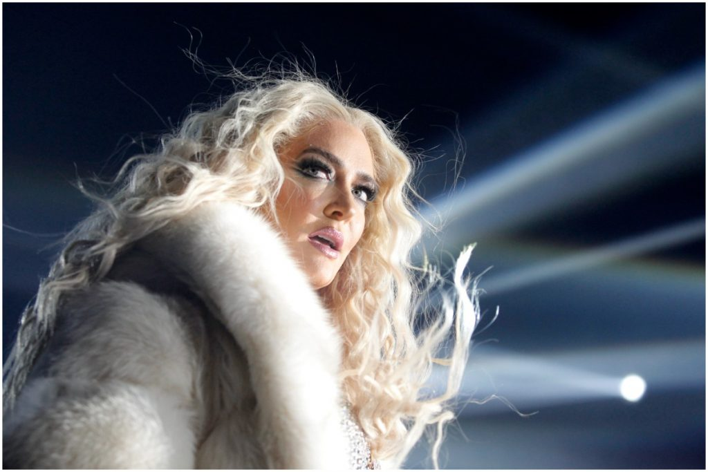 RHOBH star Erika Jayne wearing a white coat and looking away from the camera during a performance.