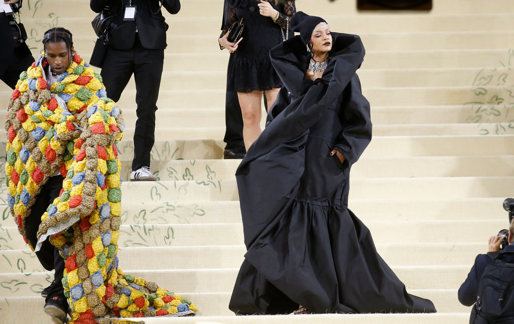 Rihanna and A$AP Rocky walk the white carpet for the MET Gala. Rihanna wears a long, black dress and Asap Rocky is covered in a colorful quit blanket.