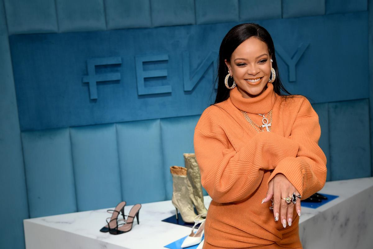Robyn Rihanna Fenty wears an orange sweater dress as she celebrates the launch of FENTY at Bergdorf Goodman at Bergdorf Goodman on February 07, 2020 in New York City.